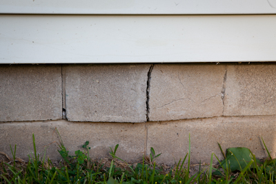 image of a foundation with I beam almost poking through the outside wall of house